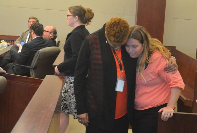 A victim's advocate comfort Kalyn Upton, the daughter of Diane Upton, who was killed in a crash caused by Rebecca Lawless, seen to the left walking toward the podium in court today, to  tender a plea and hear her sentence. (c FlaglerLive)