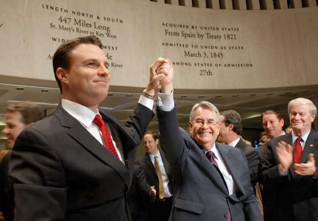 """From the left Speaker Will Weatherford, R-Wesley Chapel, and Senate President Don Gaetz, R-Destin, hold their hands high in victory as the 2014 Legislature officially ended """"sine die"""" May 2, 2014. Sen. John Thrasher looks on. (Meredith Geddings)"""