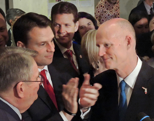 Gov. Rick Scott, right, still wields the veto pen, but the largest budget in the state's history is expected to include many perks supported by Senate President Don Gaetz, R-Destin, and Speaker Will Weatherford, R-Wesley Chapel, seen here on the last day of the Legislature last week. (Mark Foley)