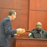 Assistant State Prosecutor Jason Lewis, left, shows FPC School Resource Deputy Jason Williams the computer the 16-year-old girl (now 17) used to write her side of the chat at the heart of the case, with another student, last December. Circuit Judge Chris France heard the case in a non-jury trial last week. A decision is expected in the next few days. (© FlaglerLive)