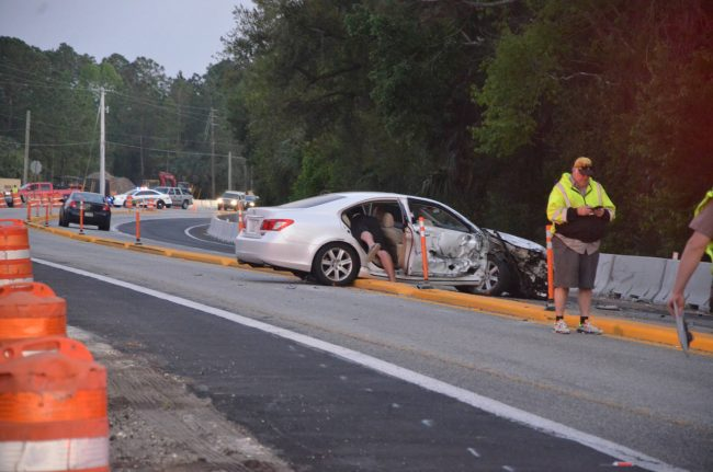 The Lexus was a distance south of the crash scene. Its occupant, seen here fetching something from the back seat, was not injured. Click on the image for larger view. (© FlaglerLive)
