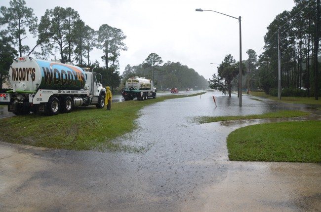 Septic tank trucks waited their turn to suck up to the lift station near the library at Palm Coast Parkway and Belle Terre, where rainfall was reported as high as 15 inches. Click on the image for larger view. (© FlaglerLive)