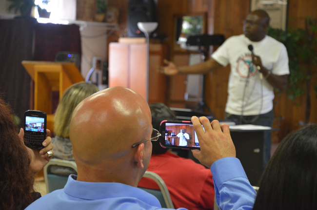 Seth Penalver, on death row for almost 19 years before his exoneration and release just 90 days ago, recorded his friend and former death row mate, Herman Lindsay, who was exonerated several years ago, as Lindsay spoke during a workshop on the death penalty in Flagler Beach Saturday. (c FlaglerLive)