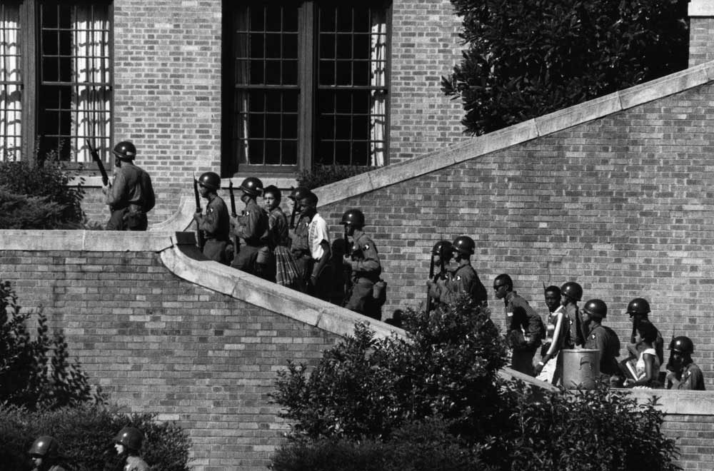 Soldiers from the 101st Airborne Division escort the Little Rock Nine students into the all-white Central High School in Little Rock, Ark.