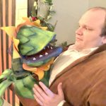 """Alexander Loucks comes under the spell of the bloodthirsty plant Audrey II in the City Repertory Theatre production of """"Little Shop of Horrors."""" (© FlaglerLive)"""