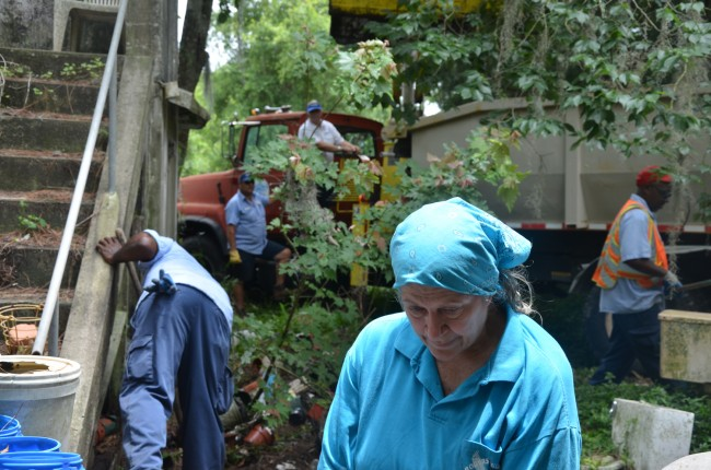 Police and city officials did not give Lynore Camp a choice: she had to make way for city workers to clean up her yard. Click on the image for larger view. (© FlaglerLive)