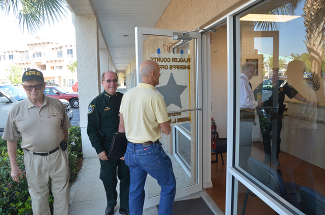 Sheriff Jim Manfre, in uniform, dedicated the new Palm Coast precinct at City Market Place with city and county officials Friday morning. The Palm Coast city offices are in the building in the background. (c FlaglerLive)