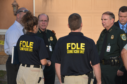 Flagler County Sheriff Jim Manfre, left, speaking with members of the Florida Department of Law Enforcement's crime lab soon after the unit arrived at the scene Friday afternoon. Undersheriff Rick Staly and Jack Bisland, the head of investigative services, are to the right. (FlaglerLive)