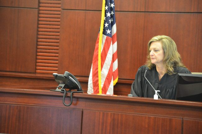 Circuit Judge Margaret Hudson spent much of today's status hearing in the Kimberle Weeks case talking to a phone, as Weeks's attorney, Kevin Kulik, spoke from his office in Ft. Lauderdale. Assistant State Attorney Jason Lewis appeared in person. Weeks herself did not. (© FlaglerLive)