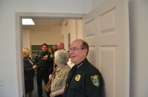 Mark Carman, toward the center of the picture, next to Mayor Jon Netts, is pointing at his new office. Carman heads the Palm Coast precinct. Click on the image for larger view. (c FlaglerLive)