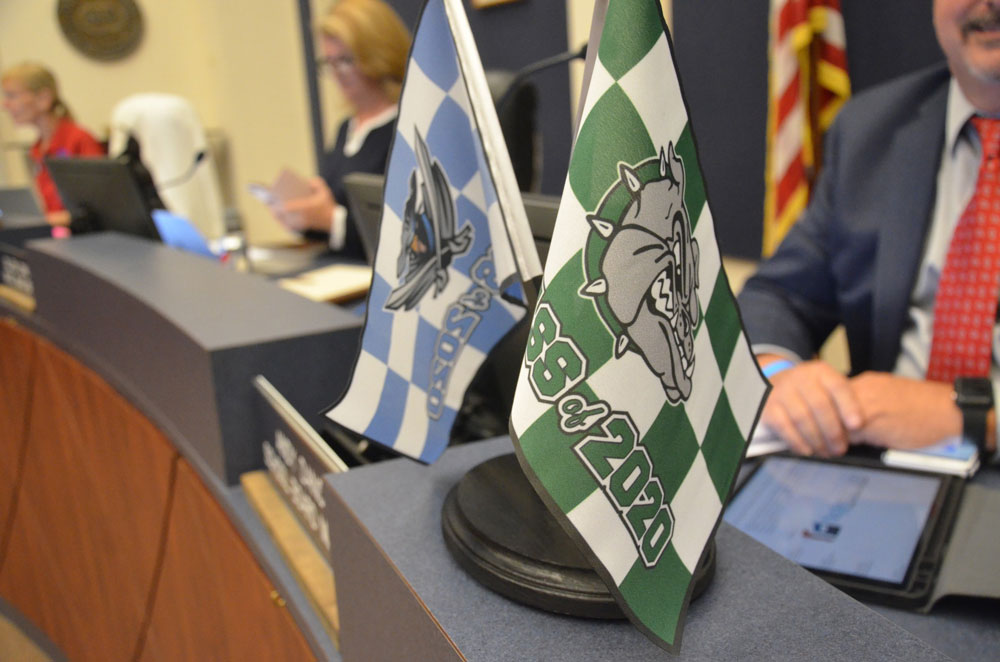 School Board member Andy Dance displayed the flags of the two high schools' Class of 2020 at a board meeting a few weeks ago. The shape of the Class of 2021 is in flux. (© FlaglerLive)