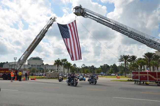 Riders streamed out of the Flagler County complex's parking lot under a giant flag draped by Flagler County Fuire Rescue and Palm Coast Fire Department personnel. Click on the image for larger view. (© FlaglerLive)