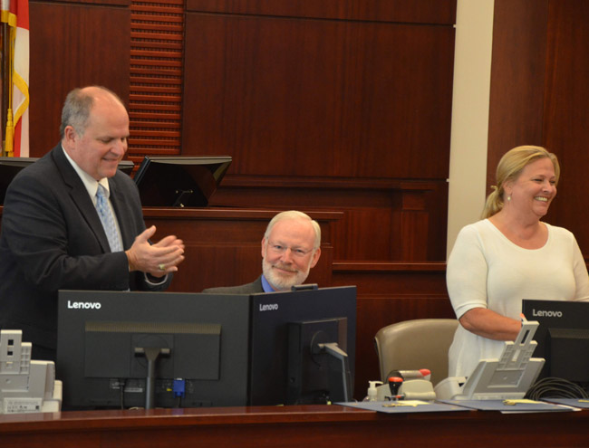 It was goodbye to Michael Greenier, center, today at the 32nd drug court graduation, as Greenier will retire from coordinating the program after serving five judges since the program's inception in 2007. He was applauded by Assistant Public Defender Bill partington, left, and Liz Williams, the now-retired Flagler Beach detective who has also always been involved in drug court. (© FlaglerLive)