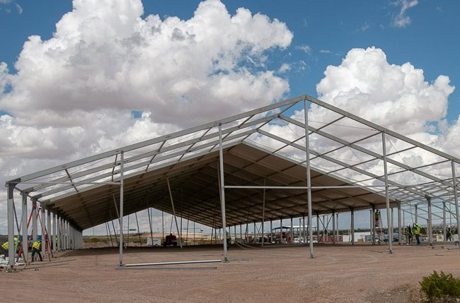 A construction crew assembles temporary soft sided facilities in El Paso, Texas, April 23, 2019. The facilities will be used for processing, care and transfer of record numbers of migrants including families and unaccompanied children