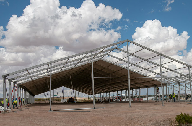 A construction crew assembles temporary soft sided facilities in El Paso, Texas, April 23, 2019. The facilities will be used for processing, care and transfer of record numbers of migrants including families and unaccompanied children crossing the border illegally.