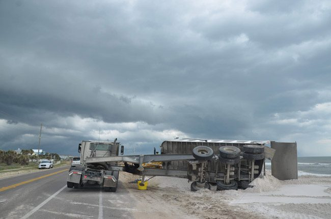 A bit of a mishap on the north A1A sea wall project last week: as the storm was gathering on Good Friday, wind blew over a dump truck, damaging its chassis. No one was hurt. Traffic was not impeded. The project carries on. (© FlaglerLive)