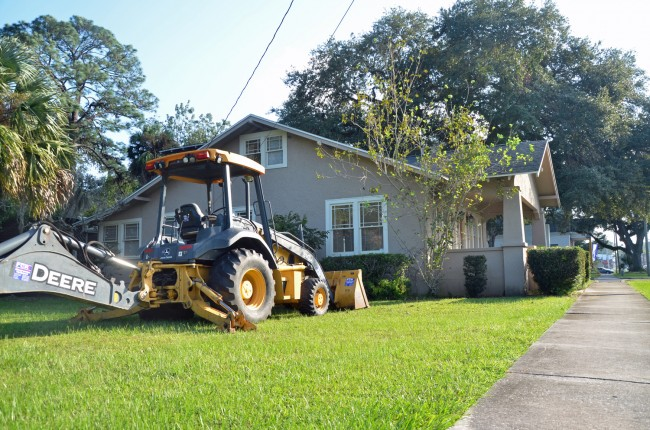 A backhoe sits ominously next to the house at 401 East Moody Boulevard, a reminder of the house's potential fate: a demolition permit is taped to its front door. (© FlaglerLive)