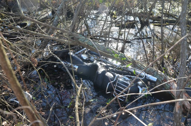 The motorcycle ended in a waterlogged ditch alongside I-95. Click on the image for larger view. (© FlaglerLive)
