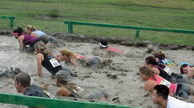 They don't call it grueling for nothing: an obstacle course requiring the contestants to crawl in mud beneath barbed wires. The author is in the pink tank top toward the right, with Priscilla Chanfrau to her right, Darci Claggett in the center of the picture, and Jane Eddy to Claggett's left, wearing No. 5079. (© Michael Eddy)