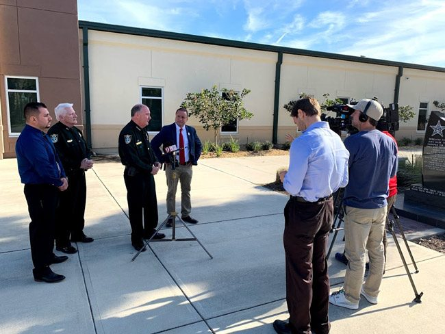 County Commissioner Joe Mullins, center, speaking with reporters outside the Sheriff's Operations Center in Bunnell in January. (© FlaglerLive)