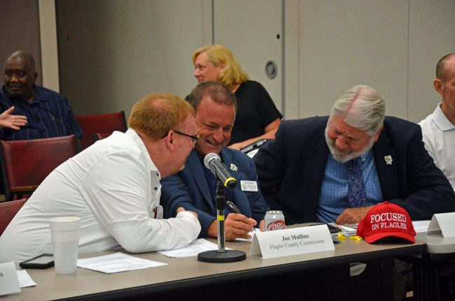 Focus on Mullins: Bunnell City Commissioner John Rogers, left, with County Commissioner Joe Mullins, center, and County Administrator Jerry Camweron this morning before the beginning of the Public Safety Coordinating Council meeting. (© FlaglerLive)