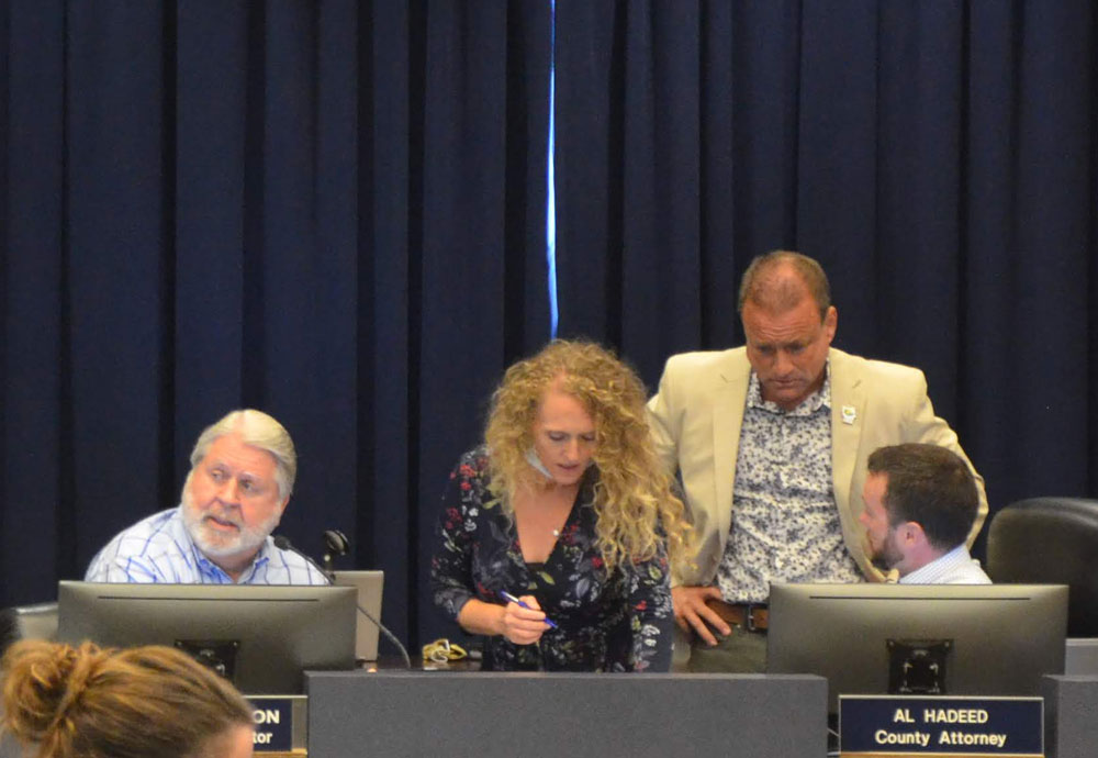 Joe Mullins, standing, right, conferring with Assistant County Attorney Sean Moylan at a meeting in June. County Administrator Jerry Cameron is to the left. Mari Davis, his assistant, is in the center. (© FlaglerLive)