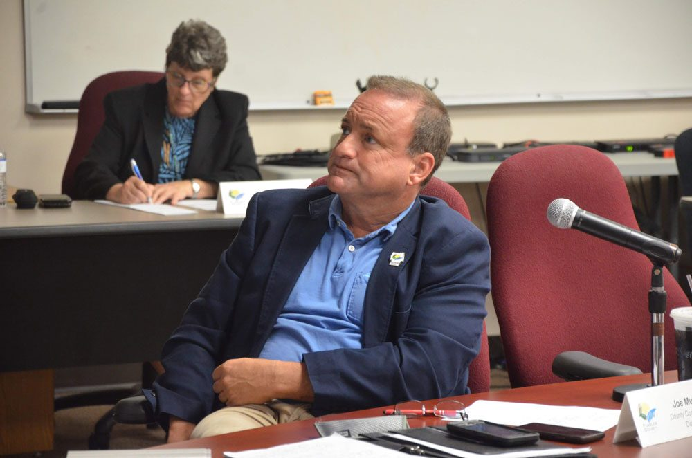 County Commissioner Joe Mullins had County PIO Julie Murphy, in the background, write a press release about a donation he made to an addiction-recovery program in Bunnell. What followed exposed a series of issues between commissioners and within county government.