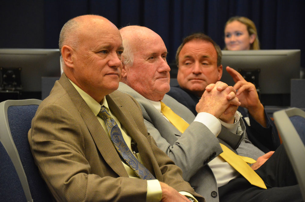 Commissioners Donald O'Brien, in the foreground, and Chairman Dave Sullivan, in the middle. Mullins, third from left, has relied on them as a shield. (© FlaglerLive)