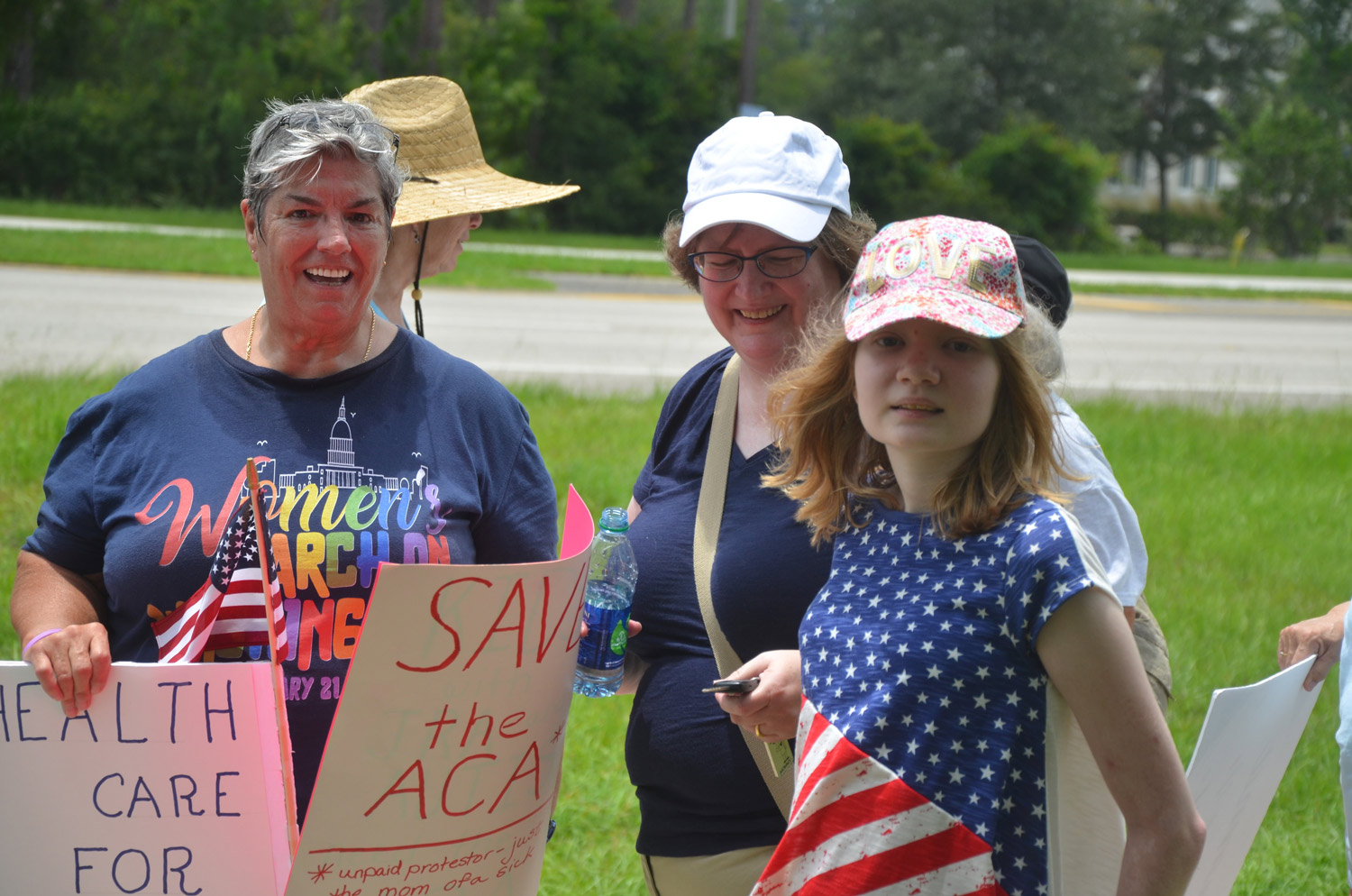 A few of today's protesters on State Road 100 by the Florida Hospital Flagler entrance: from left, Pat Ferraro, Nancy Nally, and Nally's 14-year-old daughter, Bridget. Click on the image for larger view. (© FlaglerLive)