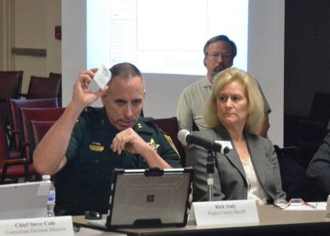 The Sheriff's Chief Paul Bovino holds up a dose of Narcan at today's meeting of the Public Safety Coordinating Council, which focused on the opioid crisis. (© FlaglerLive)