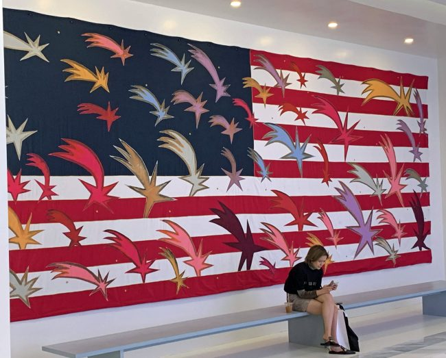 Friday is National Flag Day, which commemorates the adoption of the American flag on June 14, 1777. President Woodrow Wilson declared the first official Flag Day in 2016. Above, Frances Clemente's 'Wishing Stars,' a 2019 tapestry, hand-painted with natural dyes and stitched with embroidery and layered applique. The wooden pine bench on which the woman sits is part of the installation, currently at Hudson Yards, New York. The woman is not. Asked how he felt about sharing his work in that particular space, Clemente said: 'The audience of art is an audience of one. I hope he or she will pass by.' In that sense, the woman is very much a part of the installation. Click on the image for larger view. (© FlaglerLive)