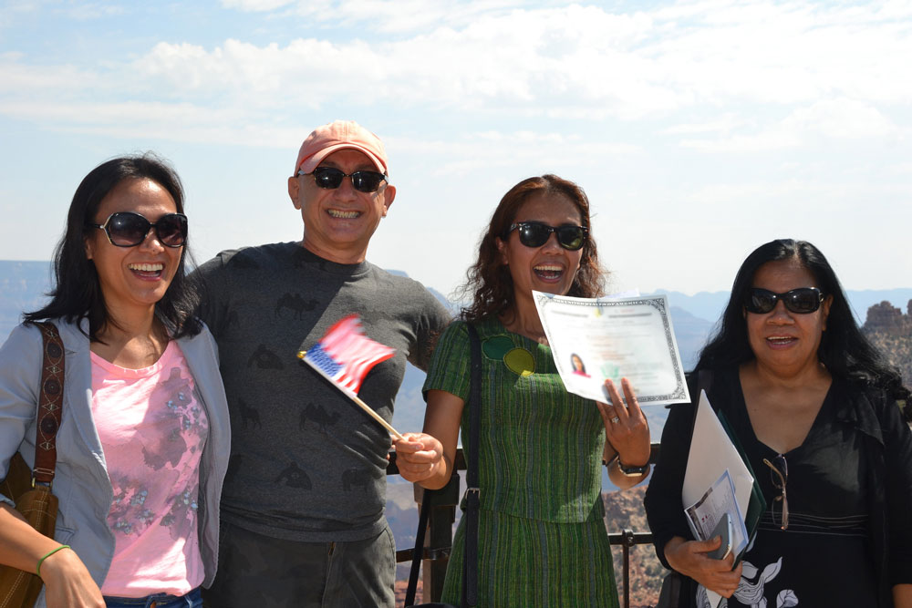 A new citizen waving her naturalization document after a ceremony at the Grand Canyon in 2016. (NPS)