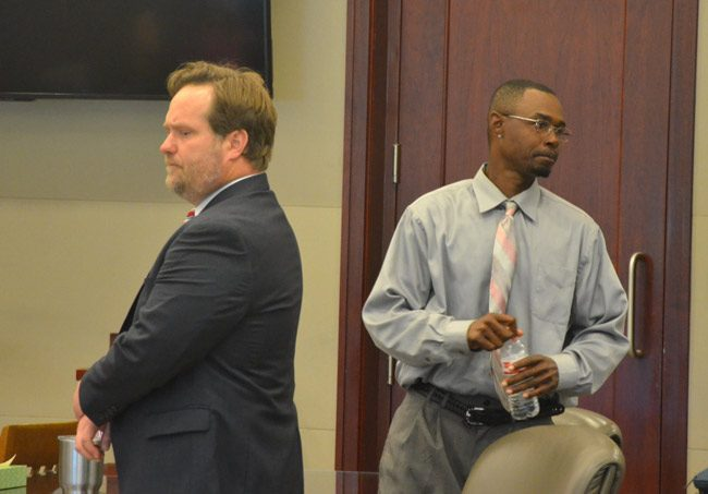 C.J. Nelson, right, moments after the verdict, looking at his family, as his attorney, Josh Davis, spoke with the judge about sentencing. (© FlaglerLive)