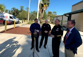 In the shadow of reporters on one side and the troubled Operations Center on the other, Wednesday afternoon: from left, union representative and sheriff's deputy Joe Barile, Chief Mark Strobridge, Sheriff Rick Staly and County Commissioner Joe Mullins. (© FlaglerLive)