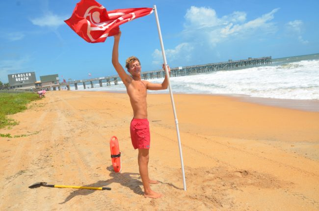 Allen, a 17-year-old Flagler Beach lifeguard, planting a no-swim flag at the north end of the pier Sunday. (© FlaglerLive)