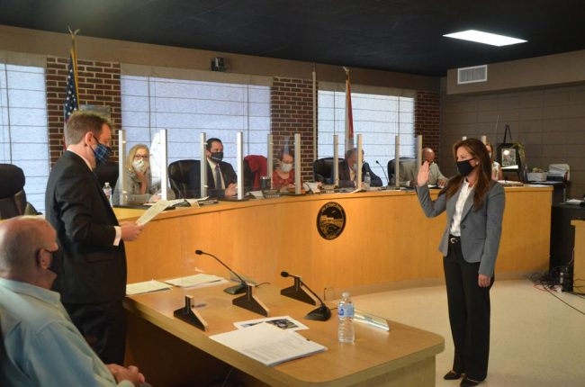 Suzie Johnston taking the oath of office, with City Attorney Drew Smith to the left and the commission looking on. (© FlaglerLive)