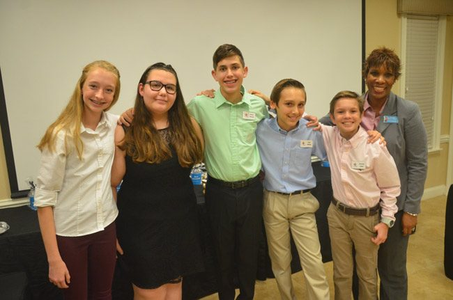 The students of Indian Trails Middle School's Open For Business, a Community Problem Solver project that aims to give small businesses a leg up. From left, Madeleine Oliva, Isabella Colindres, Daniel Wolcott, who originated the idea, Sean Gilliam and Kenneth Logan, with advisor Jearlyn Dennie. (© FlaglerLive)