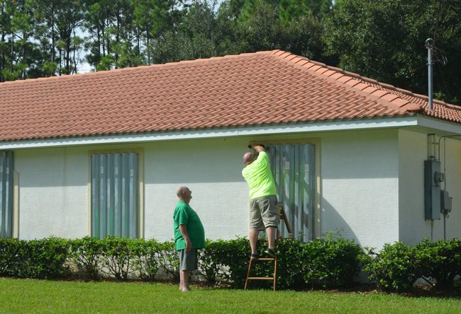 Milton Owings Jr., on the ladder, drove up from Port St. Lucie after securing his home to help secure that of his father, Milton Owins Sr., left, in Palm Coast's P Section. (© FlaglerLive)