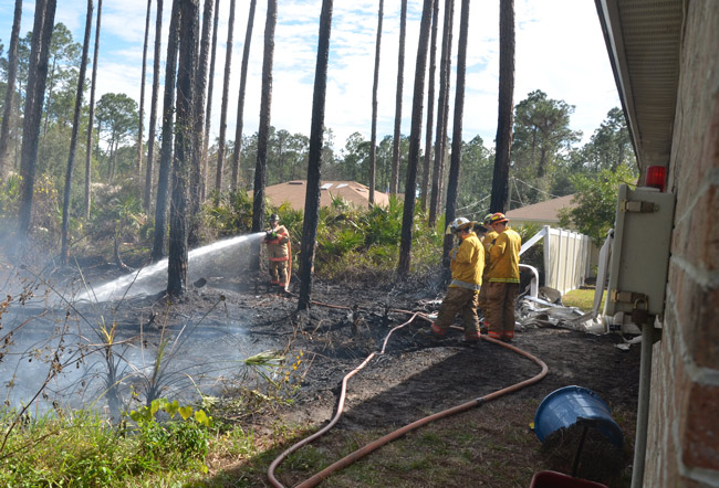 The fire was close enough to the house to melt the corner section of the fence and turn soffits into diaper-looking shreds. (© FlaglerLive)