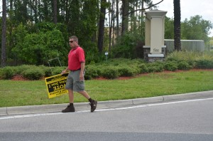 A Palm Coast Code Enforcement officer removed one of Supervisor of Elections Kimberle Weeks's signs about today's vote from a right-of-way near Town Center. The officer'[s pick-up truck was full of such signs. Click on the image for larger view. (© FlaglerLive)