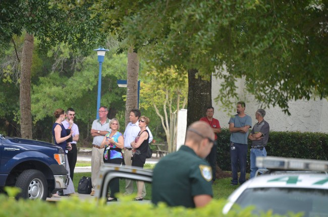 Some of Palm Coast Data's personnel stood by outside the building as the hazmat team worked. (© FlaglerLive)