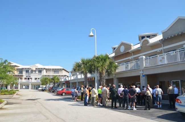 A little perspective: the new precinct's two storefronts, shown here surrounded by the people who attended today's ribbon-cutting, is just a few doors down from the city offices, on the first and third floors of the facing building. In between, on the second floor, are Hollingsworth Gallery and City Repertory Theatre. Click on the image for larger view. (c FlaglerLive)