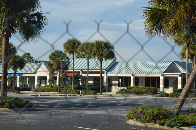 Chicken-wire fencing has gone up around a large, central segment of Palm Harbor Shopping Center, where demolition will begin later this month. (© FlaglerLive)