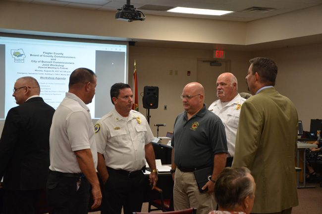 The principals in the proposed transfer of the Bunnell Fire Department to Flagler County's jurisdiction. From left, with his back to the camera, Bunnell City Commissioner John Sowell, Flagler County Fire Rescue's Joe King, Fire Chief Don Petito, Firefighters' union chief Stephen Palmer, who supports the merger, Bunnell Fire Chief Ron Bolser, and County Administrator Craig Coffey. (c FlaglerLive)