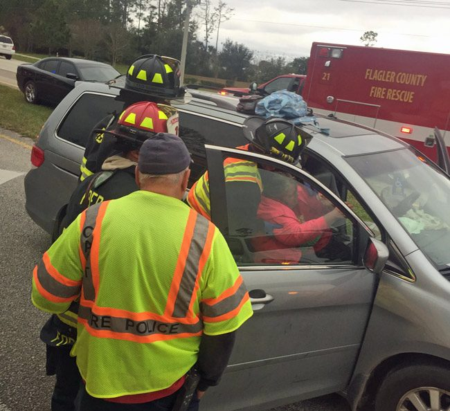 Paramedics help one of the two people injured in the crash on State Road 100 this afternoon. Both patients had leg injuries. (© FlaglerLive)