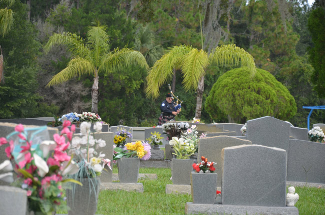 Patrick Juliano playing the bagpipes at his father's grave a few months ago, at Craig Flagler Palms cemetery. (© FlaglerLive)