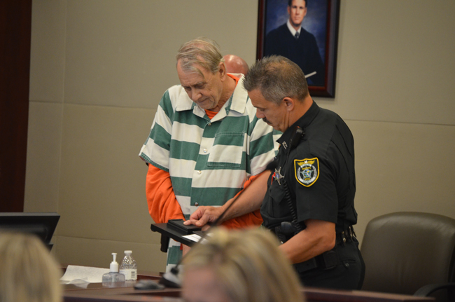 Paul Miller getting finger-printed after his sentencing in June. (© FlaglerLive)