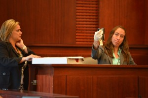 Maria Pagan, a crime lab analyst with the Florida Department of Law Enforcement, hoisted the 9 mm semi-automatic Paul Miller used to fire five bullets at Dana Mulhall. Assistant State Attorney Jacquelyn Ros is to the left. Click on the image for larger view. (© FlaglerLive)