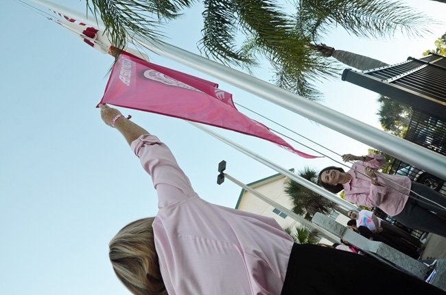 Flagler County Commissioner Barbara Revels and School Board member Colleen Conklin raised the Pink Army flag at a ceremony at the County Administration building this morning. (© FlaglerLive)