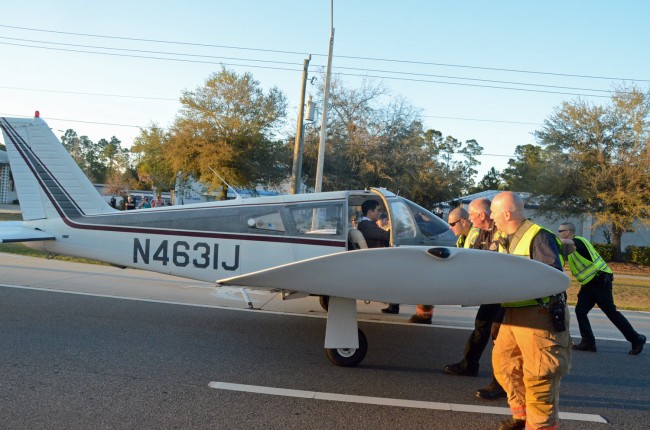 With Joo Lee at the controls, cops and first responders pushed the plane off of Palm Coast Parkway. Click on the image for larger view. (© FlaglerLive)